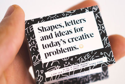 A matchbook being held in someone's hand that reads: Shapes, letters and ideas for today's creative problems.