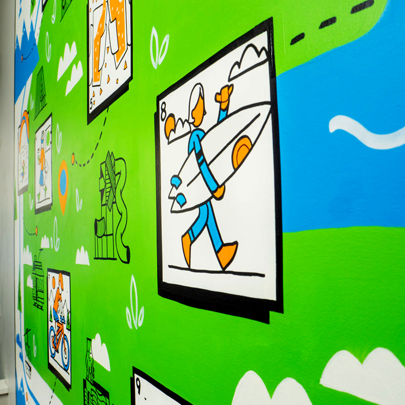 Close-up wall mural painting shows an illustrated surfer headed to the water