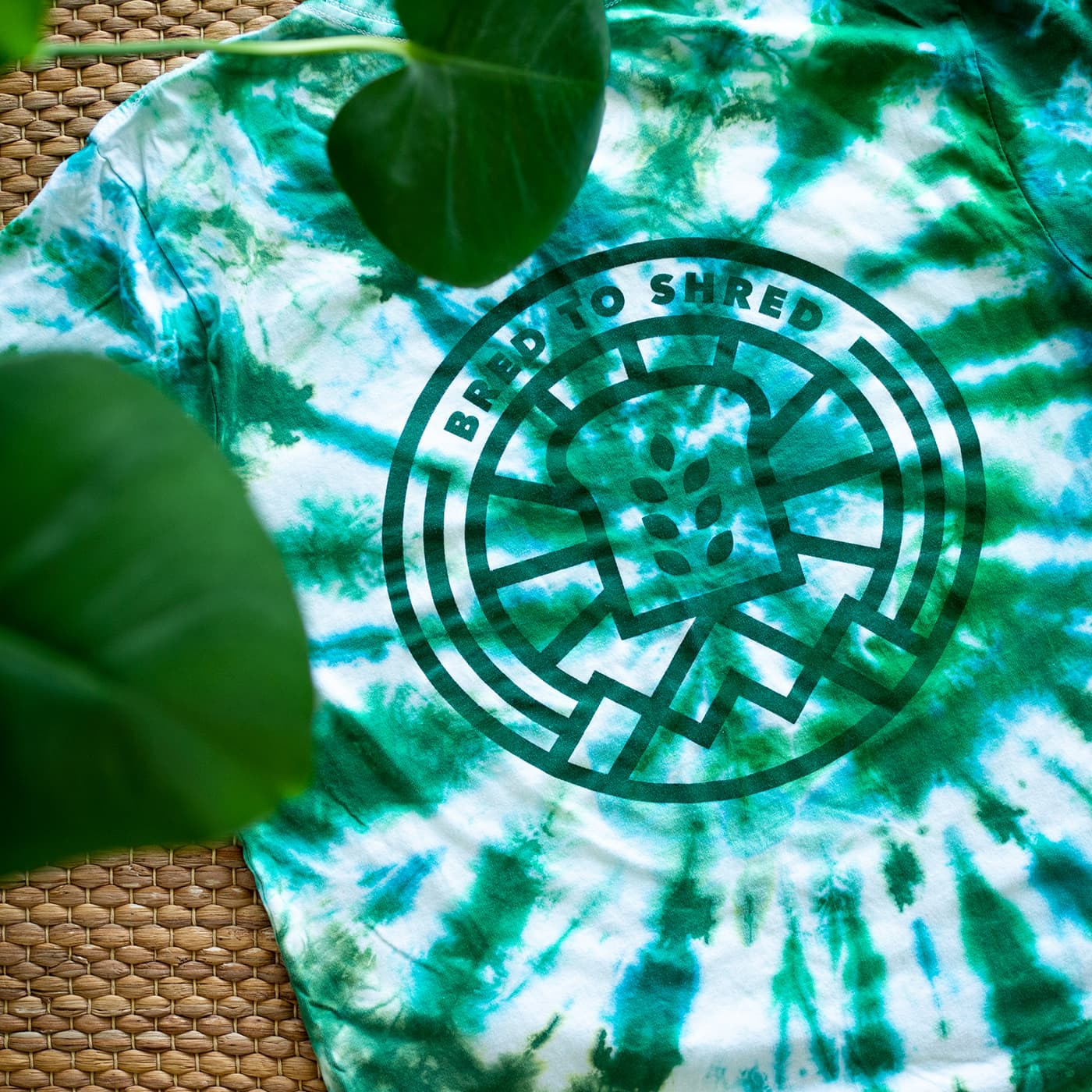 Blue, green and white tie-dyed t-shirt with a circular slice of bread logo and the words: Bred to Shred on its back