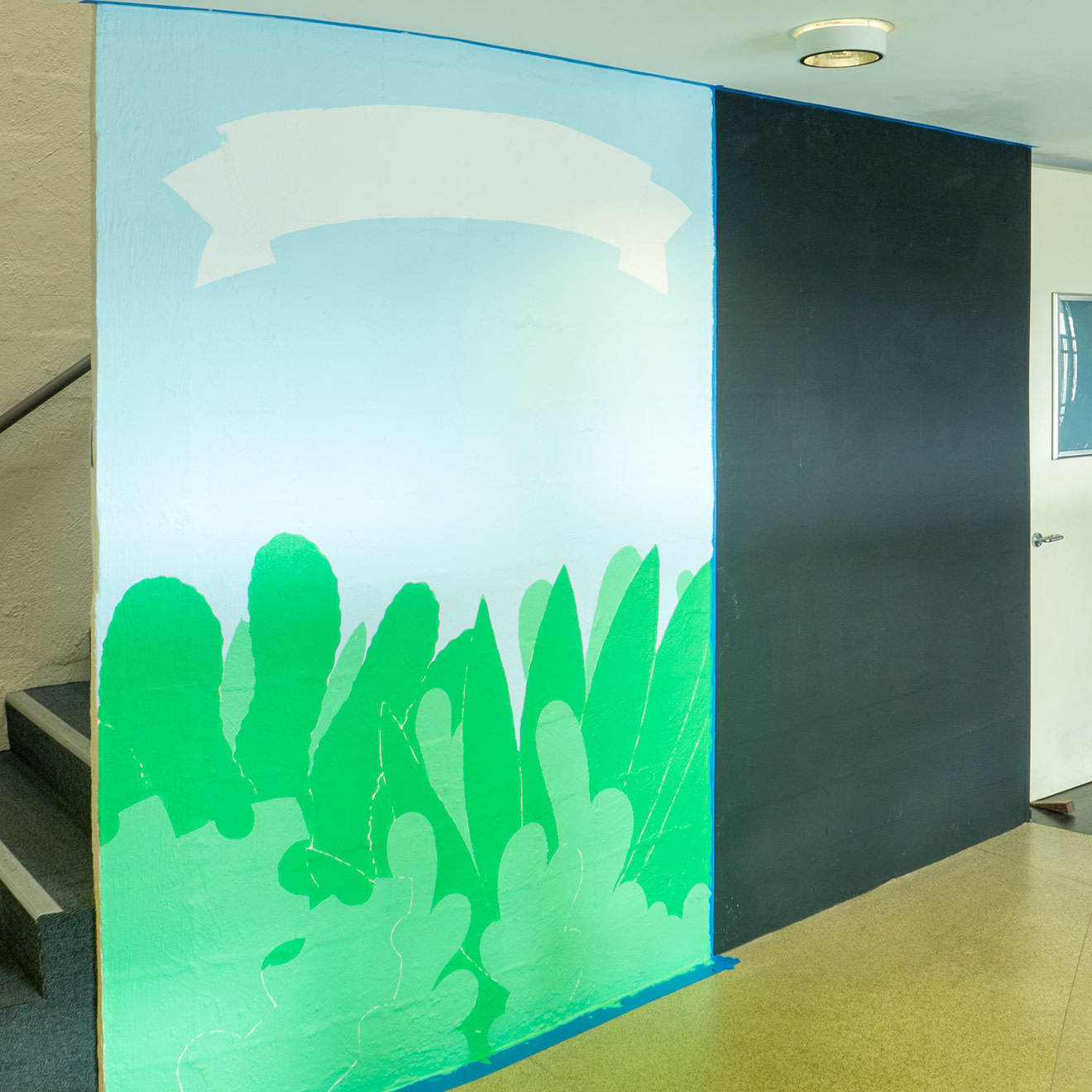 Work in progress of a mural painting featuring trees and blue sky