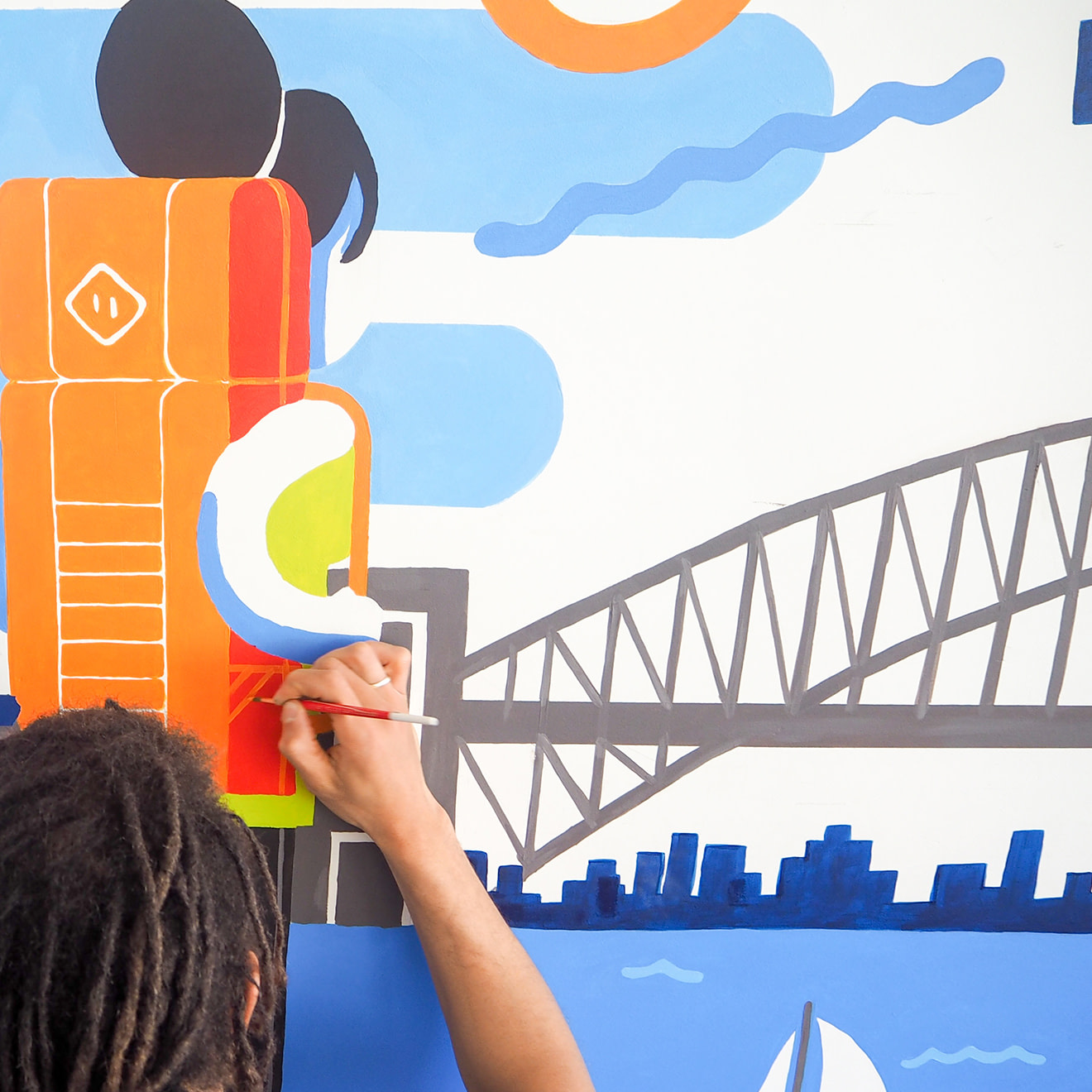 Man painting an orange backpack on a woman as part of a larger mural scene.