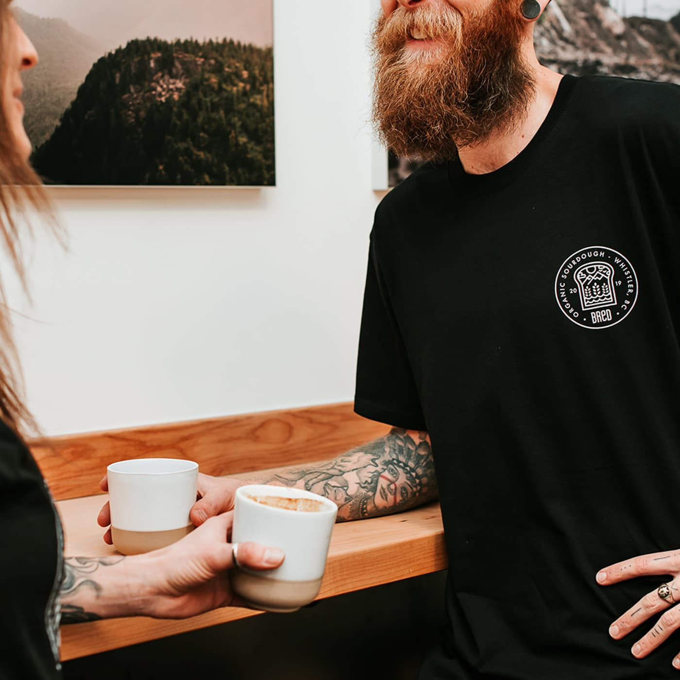Man and woman leaning on a bench drinking lattes and wearing black t-shirts