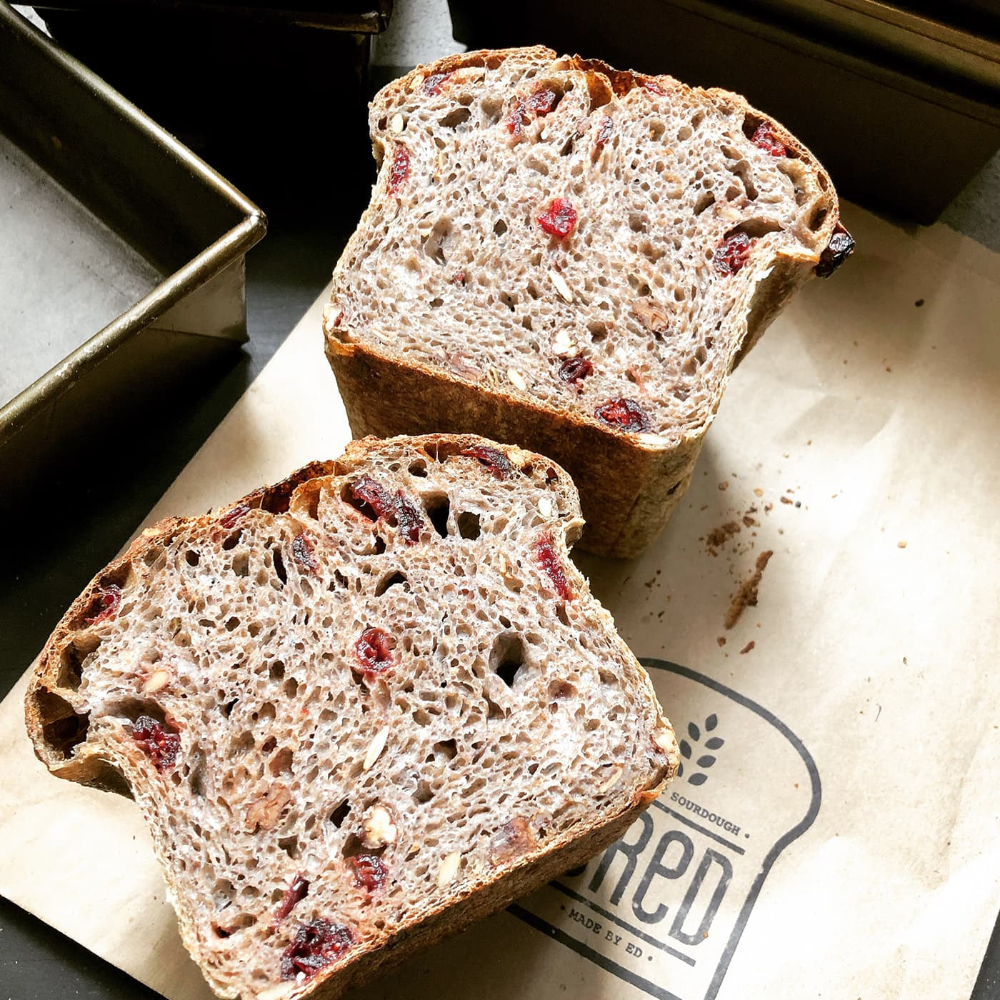 A loaf of bread sliced in two. There are cranberries and nuts insides the loaf.