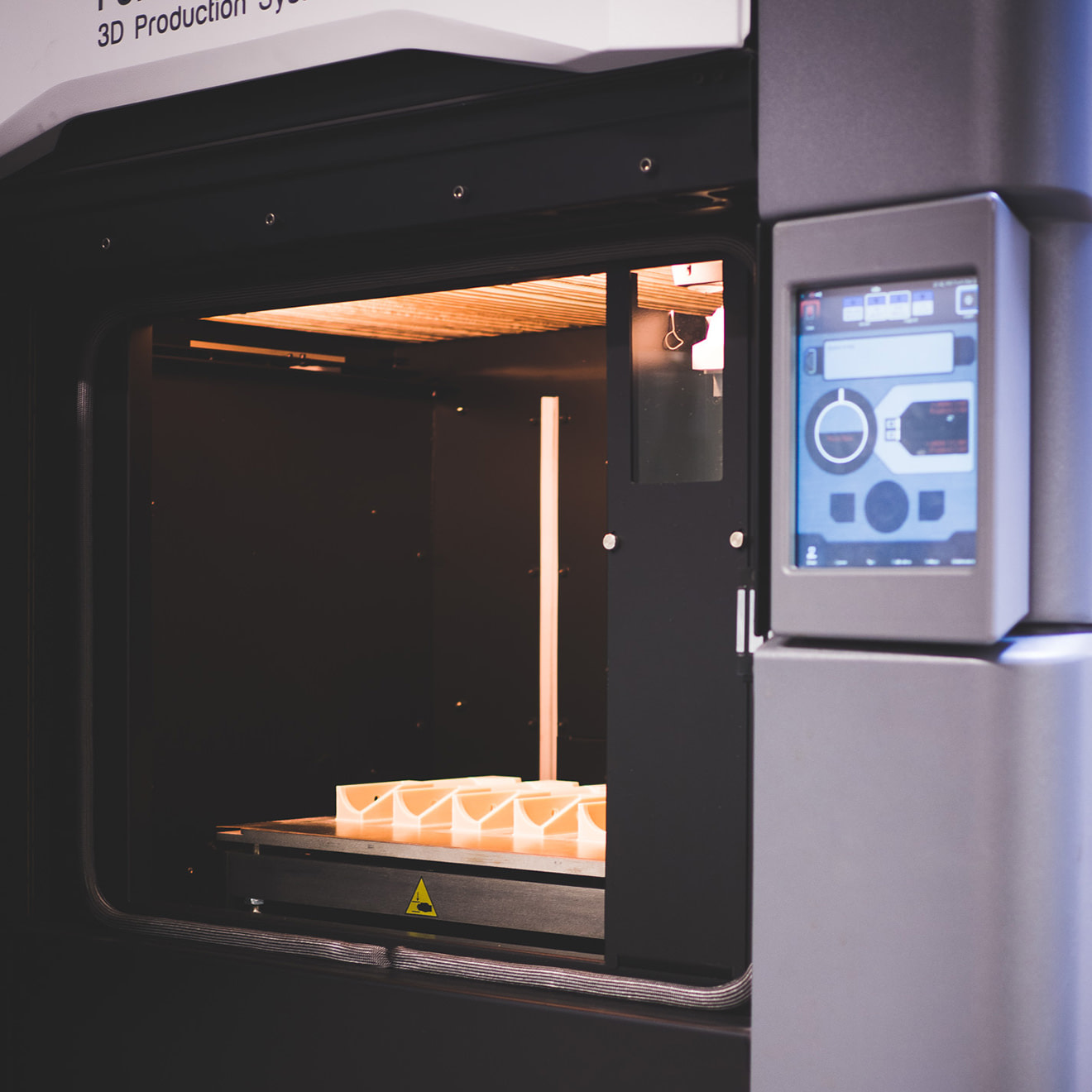 A 3D printer in use making something with orange plastic