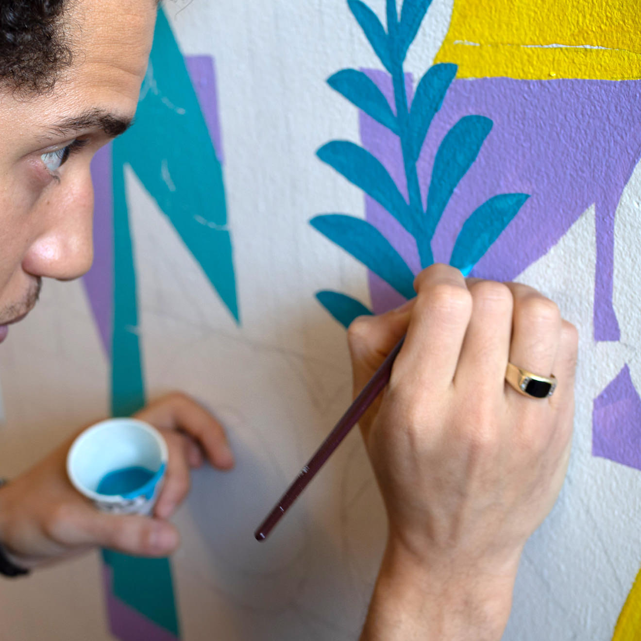 Man painting blue leaves onto a wall mural
