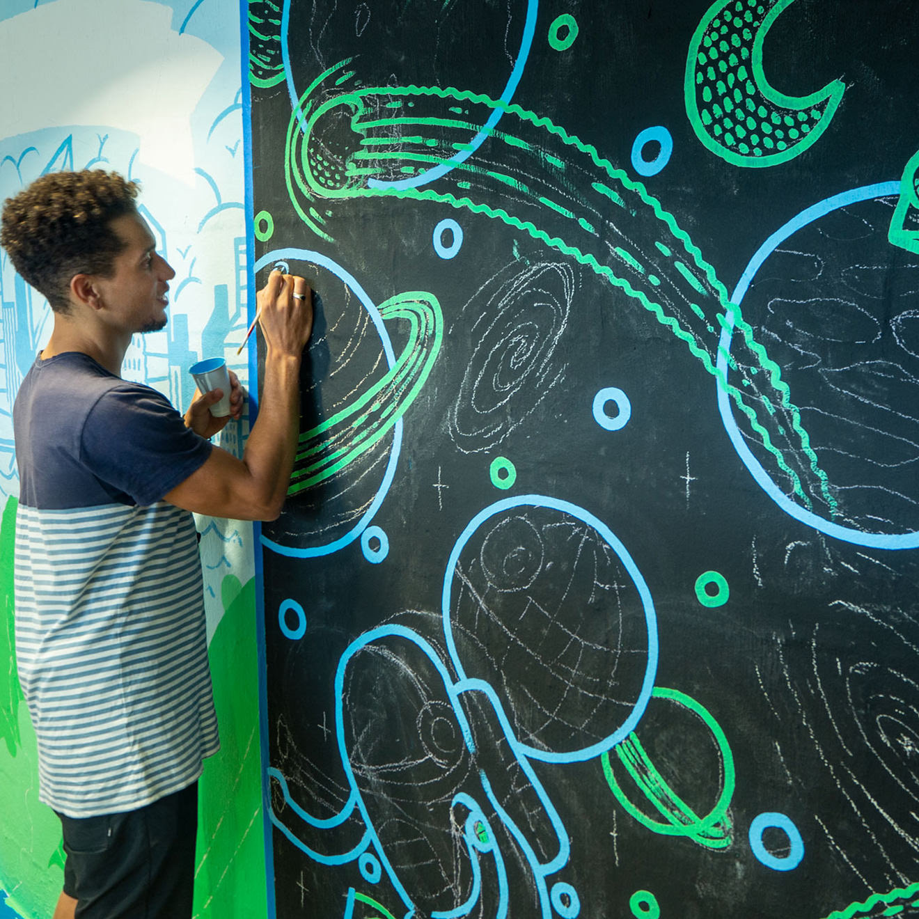 Man painting a blue-ringed planed onto a dark wall as part of a larger mural