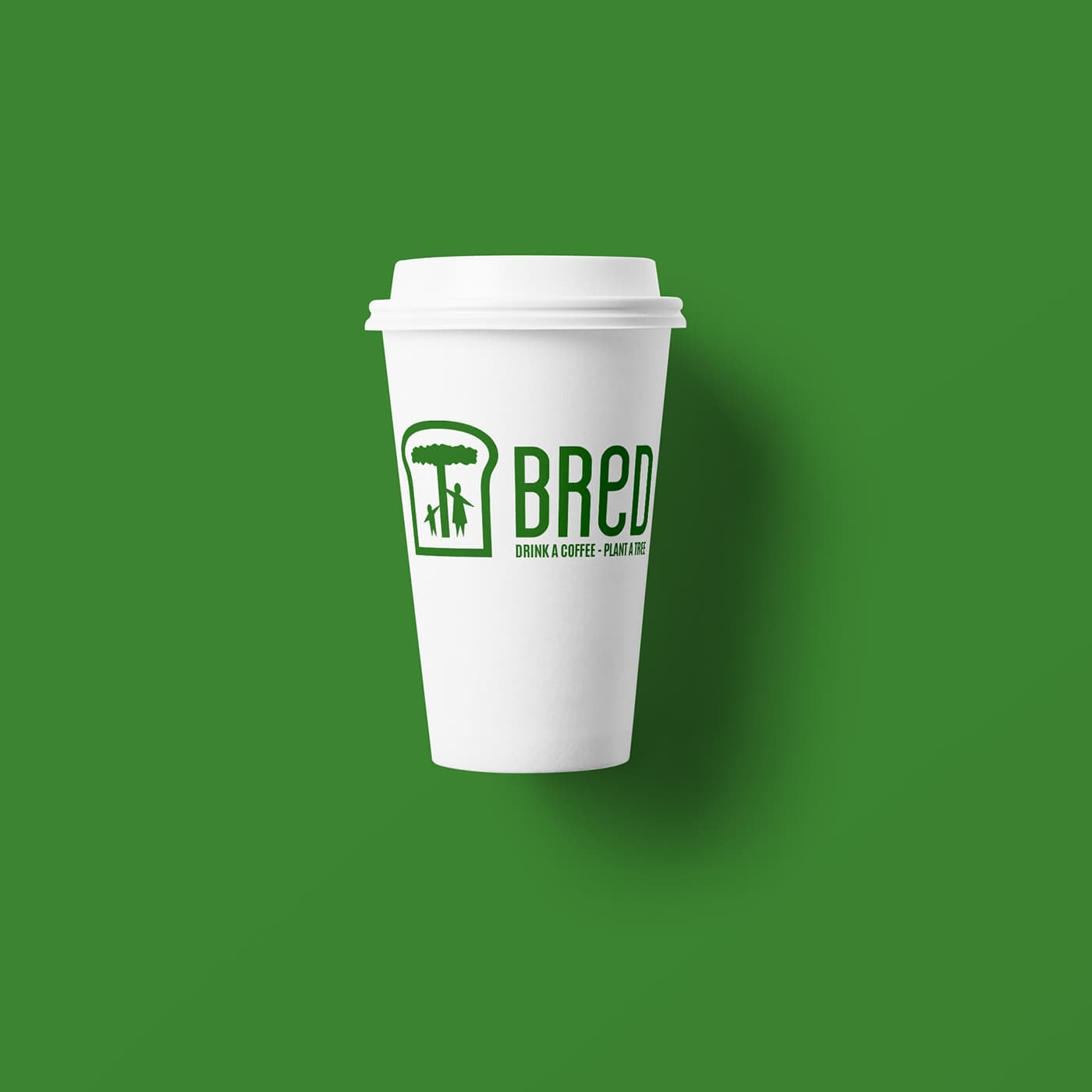 A white takeout coffee cup with green writing on it that reads: Bred - drink a coffee, plant a tree