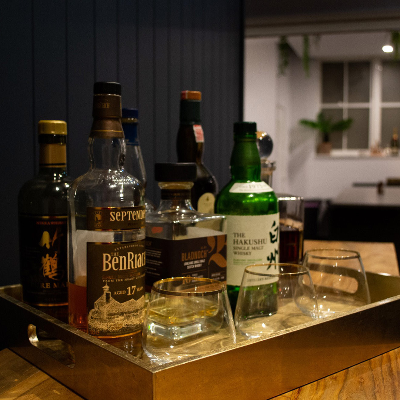 A bar cart with whisky and bourbon and a couple glasses
