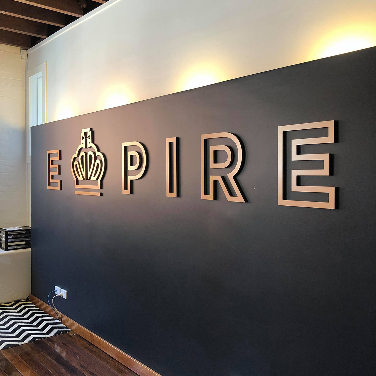 The EMPIRE bronze logo atop a black dividing wall in an office